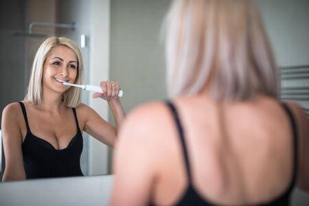 Pretty, middle aged woman brushing her teeth in a modern design bathroom Reklamní fotografie