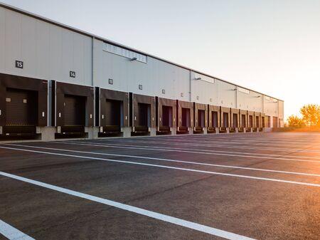 Extérieur de l'entrepôt avec rampes de chargement et emplacements pour camions à garer - bâtiment de stockage d'entrepôt de l'industrie moderne.