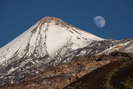 Colorful scenic landscape of moon rise in Tenerife national park of Teide. El Teide with moon rising by its side. Stock Photo