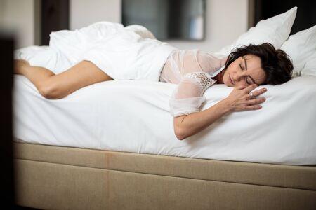 Beautiful young woman sleeping on bed at bedroom, getting a good night sleep Stok Fotoğraf - 137884490