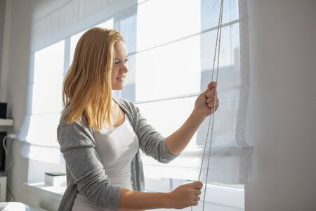 Pretty, young woman lowering the interior shades/blinds in her modern interior apartment Imagens