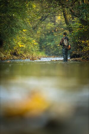 Fly fisherman fly fishing on a splendid mountain river 写真素材