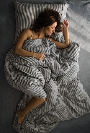 Pretty, young woman in her bed, fast asleep. Importance of sleep concept Stok Fotoğraf - 137884911