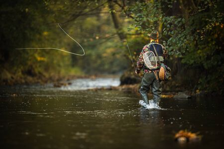 Close-up view of the hands of a fly fisherman holding a lovely trout while fly fishing on a splendid mountain river