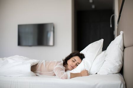 Beautiful young woman sleeping on bed at bedroom Stock fotó