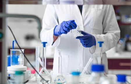 Researcher carrying out scientific research in a lab (shallow DOF; color toned image)