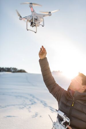 Young man controlling his drone in snowy outdoors. Drone operator holding a transmitter and landing with a drone.