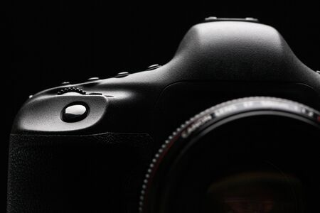 Professional modern DSLR camera low key stock photo/image - Modern DSLR camera with a very wide aperture lens on with highlighted edges against black background