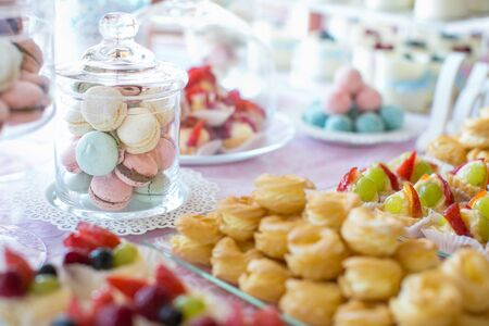 Wedding Reception Table setting. Colorful macarons and cakes.