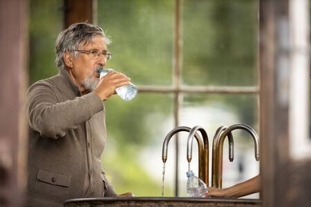 Handsome senior man drinking mineral water in a spa/health resort, enjoying its health benefits