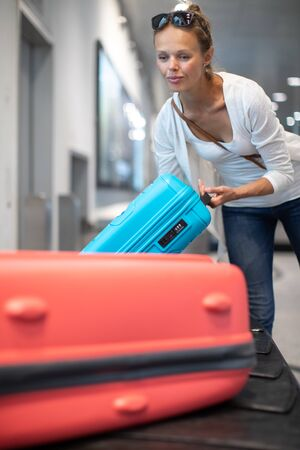 Young woman with her luggage at an international airport, waiting for her luggage to arrive at the baggage claim zone