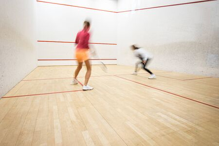 Two female squash players in action on a squash court (motion blurred image; color toned image)