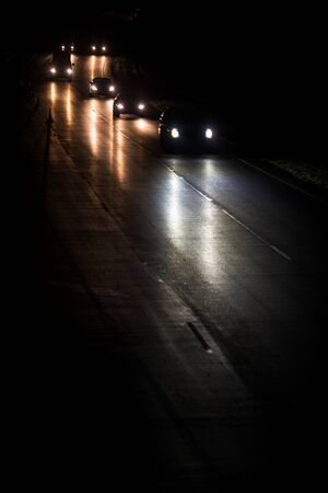 Busy highway at night with cars of commuters going home from work Imagens