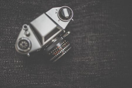 Old retro camera on vintage wooden boards abstract background with lens, close-up photo of old camera lens, image is retro filtered, selective focus
