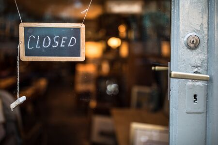 Closed - sign hanging on glass door of a shop in a city Stock Photo
