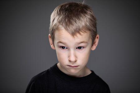 Grief-stricken little boy - feeling intense sorrow, remorse, sadnesss - studio portrait - vivid emotions series