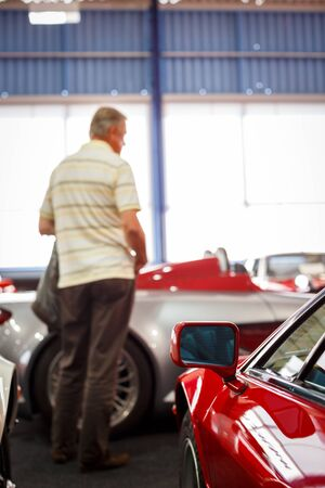 Old cars auction - People viewing cars on sale during an expensive old cars  auction