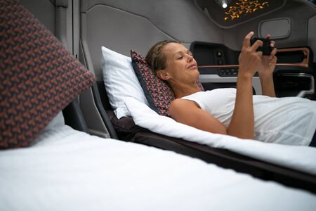 Pretty, young woman abord a first class commercial flight using their cell phone during flight