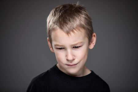 Grief-stricken little boy - feeling intense sorrow, remorse, sadnesss - studio portrait - vivid emotions series
