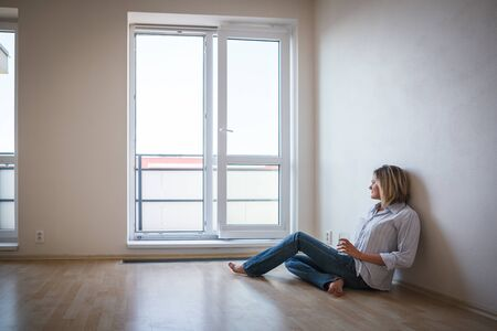 Just moved in: pretty, young woman having a drink in her brand new modern apartment