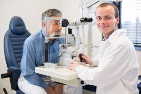 Optometry concept - pretty young woman having her eyes examined by an eye doctor Banque d'images