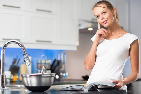 Pretty, young woman in her modern, clean and bright kitchen, fixing lunch (color toned imagey; shallow DOF)