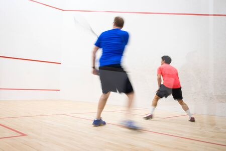 Squash players in action on a squash court (motion blurred image; color toned image) Foto de archivo