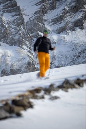 Winter sports - young man walking with snowshoes uphill in high mountains covered with lots of snow (selective focus on the mountain in the background) Foto de archivo