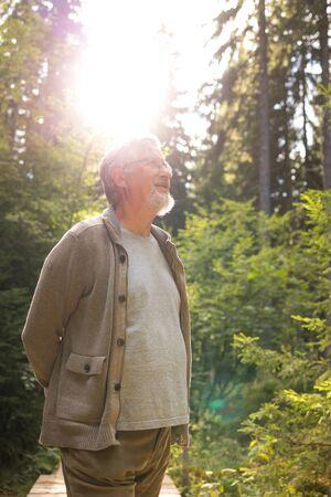 Senior man enjoying the outdoors, hiking, walking throught lovely nature