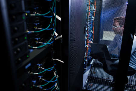 Data center employee running tests on the server computers, dealing with an urgent issue, security breach, updateing the system (color toned image)