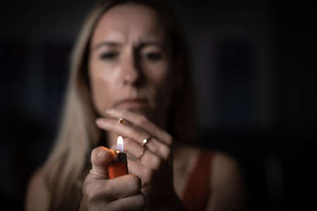 Mid-aged woman lighting a cigarette at home, getting her nicotine daily dose