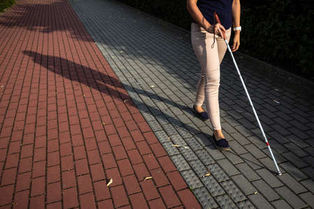 Blind woman walking on city streets, using her white cane