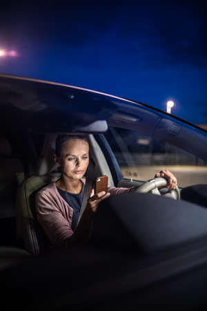 Young female driver playing with her cellphone instead of paying attention to driving startled in a potentially dangerous situation - Road safety concept Stock Photo