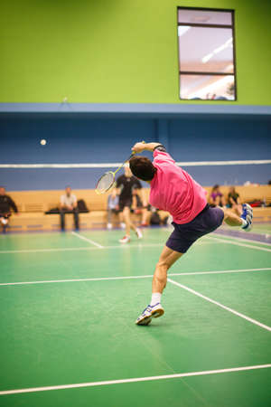 Male badminton player in the middle of a fast paced badminton rally