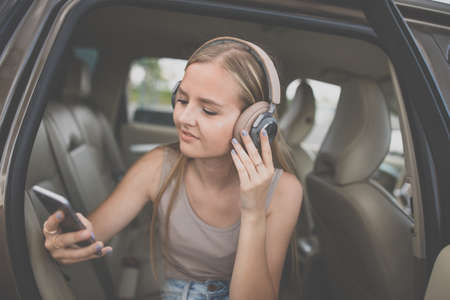 Cute teenage girl listening to her favorite music/audiobook on hig-end headphones during a roadtrip