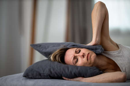 Sleepless lady covering ears with pillow. Noisy neighbors, tinnitus, insomnia or stress concept. Tired woman can't sleep. Awake in bed after coming home from her shifh, work. Noise from party next door. Stock fotó