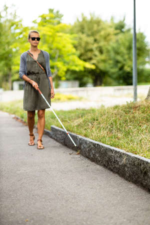Blind woman walking on city streets, using her white cane to navigate the urban space better and to get to her destination safely Banque d'images