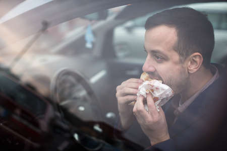 Handsome young man eating a hurried lunch in his car (color toned image; shallow DOF) Stock Photo