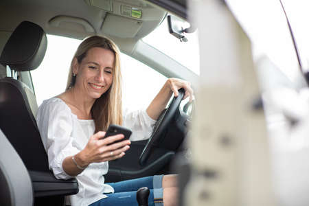 Pretty middle aged woman having at the wheel of her car, using a smartphone Standard-Bild