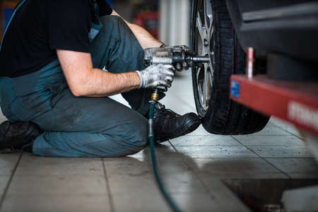 Car mechanic changing tires of a car in a repair shop,car garage (shallow DOF, colour toned image)