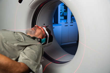 Senior man going through a Computerized Axial Tomography (CAT) Scan medical test/examination in a modern hospital (color toned image; shallow DOF) Stockfoto