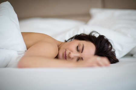 Beautiful young woman sleeping in bed in the morning, catching up on her lack of sleep