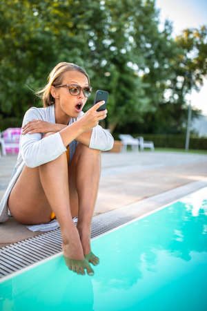 Young Beautiful Suntanned Woman wearing sunglasses relaxing next to a Swimming Pool  on a lovely Summer Day Standard-Bild