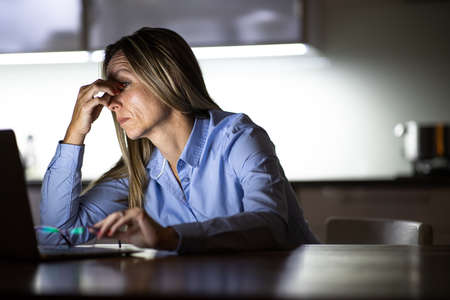 Pretty, middle-aged woman working late in the day on a laptop computer at home, running a business from home, working remotely - getting frustrated, exhausted