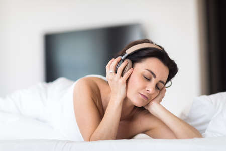 Pretty, young woman listening to music on her hi-fi headphones in bed, relaxing