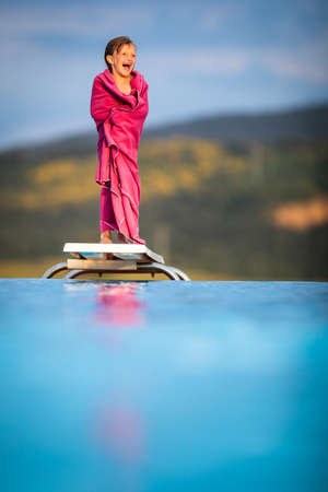 Little girl on a pool's edge, learning to swim and dive. Swimming with kids. Healthy sport activity for children. Sun protection. Water fun. Standard-Bild