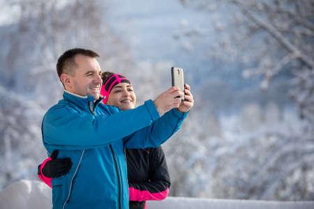 Young woman and cheerful man on christmas holidays, ejoying snow Standard-Bild
