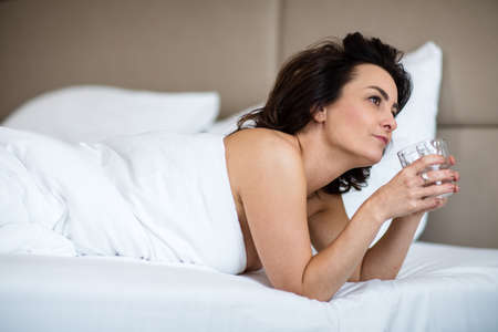 Beautiful young woman drinking water in bed first thing in the morning