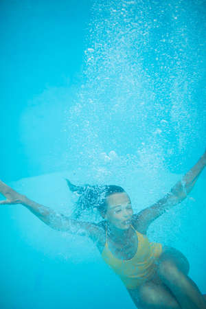 Gorgeous young woman in a pool, jumping and diving underwater, having fun