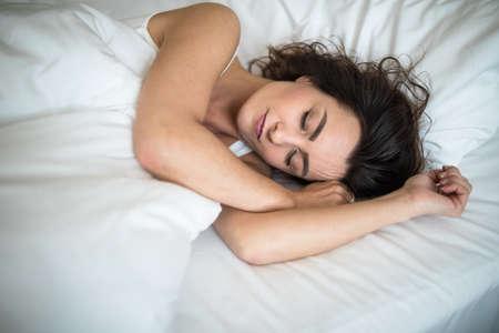 Beautiful young woman sleeping on bed at bedroom Standard-Bild